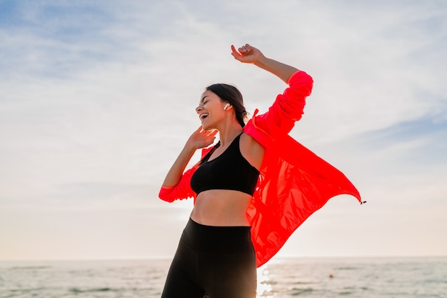 Jonge lachende aantrekkelijke slanke vrouw doet sport in de ochtend zonsopgang dansen op zee strand in sportkleding, gezonde levensstijl, luisteren naar muziek op oortelefoons, roze windjack dragen, plezier maken