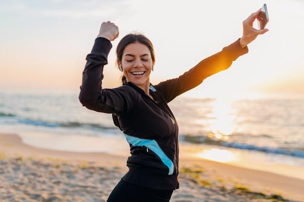 Jonge lachende aantrekkelijke slanke vrouw sport oefeningen doen op ochtend zonsopgang strand in sportkleding, gezonde levensstijl, luisteren naar muziek op oortelefoons, selfie foto op telefoon er sterk uitzien