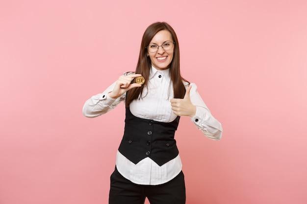 Jonge lachende aantrekkelijke zakenvrouw in glazen met bitcoin en duim opdagen geïsoleerd op pastel roze achtergrond. dame baas. prestatie carrière rijkdom concept. kopieer ruimte voor advertentie.