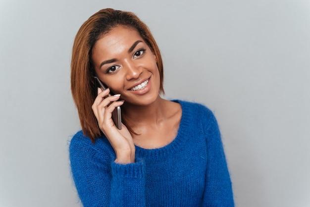 Jonge lachende afrikaanse vrouw in trui praten aan de telefoon
