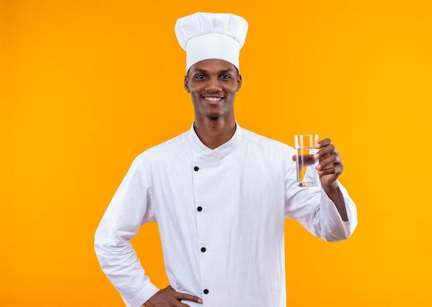 Jonge lachende afro-amerikaanse kok in uniform chef houdt glas water en legt hand op taille geïsoleerd op oranje muur