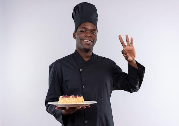 Jonge lachende afro-amerikaanse kok in uniform chef-kok houdt cake op plaat en gebaren ok handteken op wit met kopie ruimte