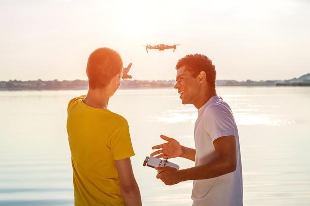 Jonge lachende afro-amerikaanse man en zijn blanke vriend die drone met controller bedient, staande bij de rivier bij zonsondergang