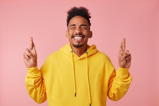 Jonge lachende afro-amerikaanse man in gele hoodie, hief zijn handen en kruiste zijn vingers en hoopt op geluk, staat met kopie ruimte.