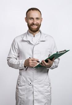 Jonge lachende arts met map en pen in witte jas.