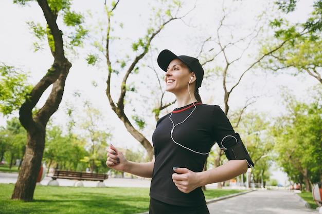 Jonge lachende atletische brunette vrouw in zwart uniform en pet met koptelefoon training doen van sport, hardlopen en luisteren naar muziek op pad in stadspark buitenshuis