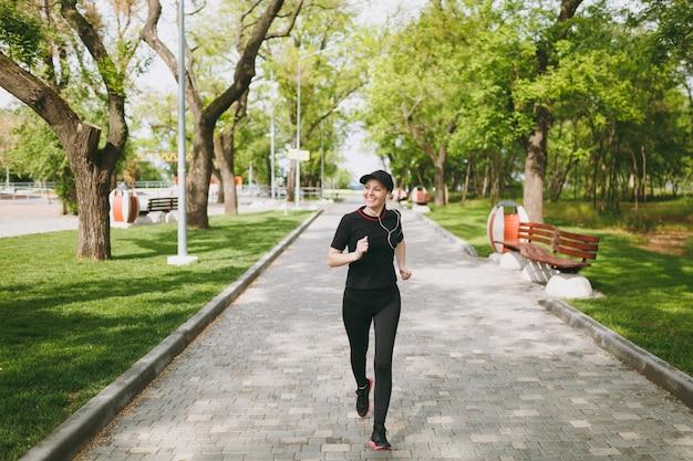Jonge lachende atletische brunette vrouw in zwart uniform en pet met koptelefoon training doen van sport, hardlopen, joggen, luisteren naar muziek op pad in stadspark buitenshuis