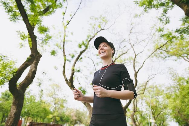 Jonge lachende atletische brunette vrouw in zwart uniform en pet met koptelefoon training sport doen, hardlopen en luisteren naar muziek op pad in stadspark buitenshuis