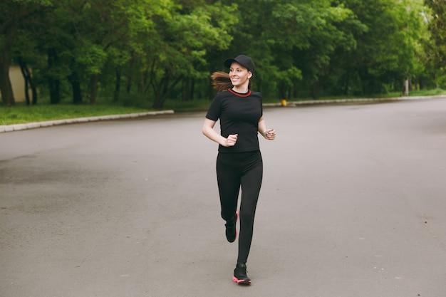 Jonge lachende atletische mooie brunette vrouw in zwart uniform, cap training sport oefeningen doen, hardlopen, joggen, opzij kijken op pad in stadspark buitenshuis