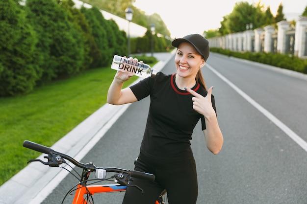 Jonge lachende atletische sterke vrouw in zwart uniform, pet houden wijzend op fles water, weg rijden op de fiets buiten op lente of zomer zonnige dag. fitness, sport, gezonde levensstijl concept.