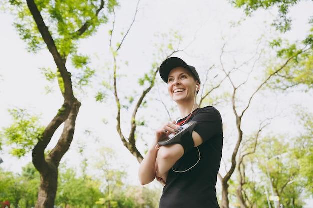Jonge lachende atletische vrouw in zwart uniform met koptelefoon luisteren naar muziek, met behulp van applicatie, app voor hardlopen of joggen op mobiele telefoon, training in stadspark buitenshuis
