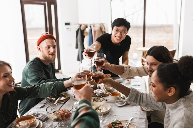 Jonge lachende aziatische man in brillen en zwart t-shirt proost glazen wijn met collega's
