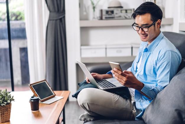 Jonge lachende aziatische man ontspannen met behulp van laptopcomputer werken en videoconferentie vergadering thuis. jonge creatieve man kijken scherm typen bericht met smartphone. werk vanuit huis concept