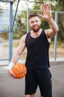 Jonge lachende bebaarde basketbalspeler die iemand begroet met de hand buiten zwaaiend