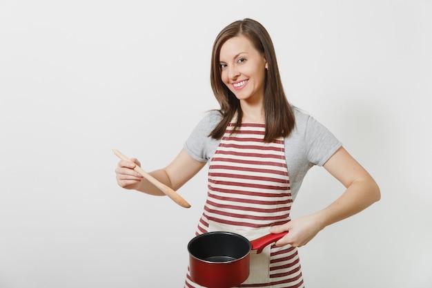Jonge lachende blanke huisvrouw in gestreepte schort, grijs t-shirt geïsoleerd. mooie huishoudster vrouw met proeverij rode lege stoofpan houten lepel