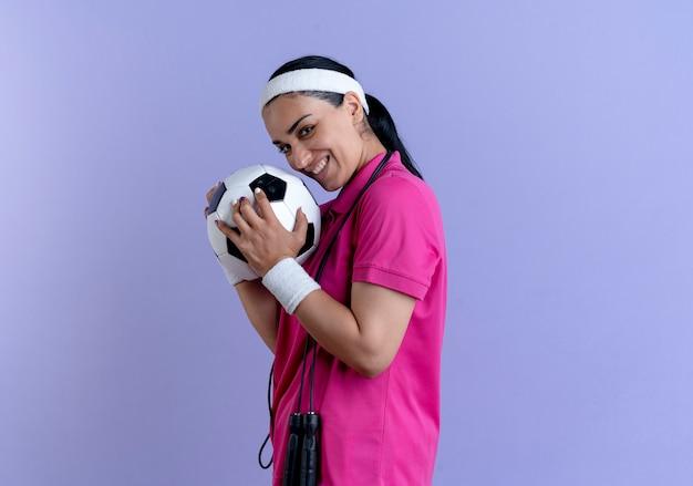Jonge lachende blanke sportieve vrouw met hoofdband en polsbandjes staat zijwaarts bal vast te houden