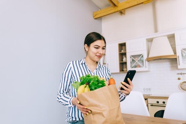 Jonge lachende blanke vrouw gebruik smartphone in de moderne keuken, tas met verse groente op tafel. online eten en boodschappen kopen.