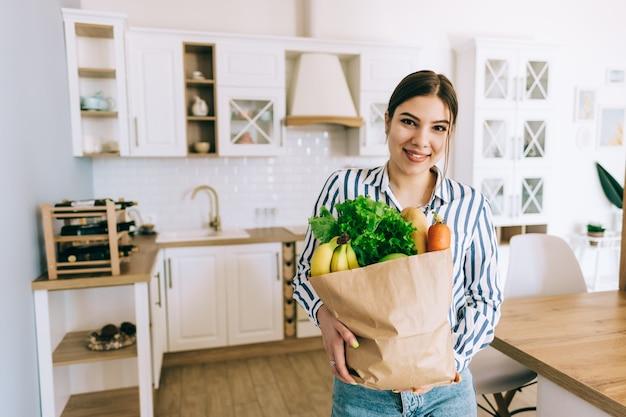 Jonge lachende blanke vrouw houdt eco boodschappentas met verse groenten en stokbrood in moderne keuken.