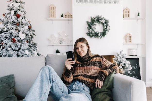 Jonge lachende blanke vrouw met behulp van mobiele telefoon in vakantie thuis op de bank.