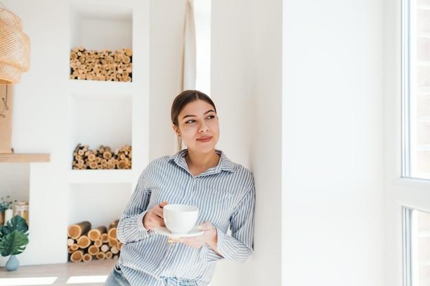 Jonge lachende blanke vrouw stond in de buurt van het raam met een kopje koffie en genietend van de zonnige ochtend.