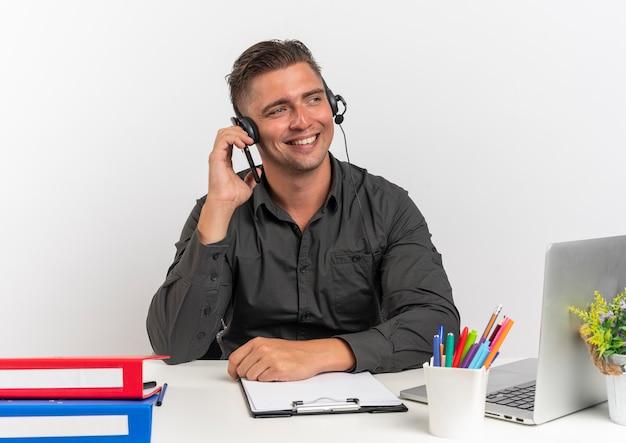 Jonge lachende blonde kantoor werknemer man op koptelefoon zit aan bureau met office-hulpprogramma's met behulp van laptop kijkt naar kant geïsoleerd op een witte achtergrond met kopie ruimte