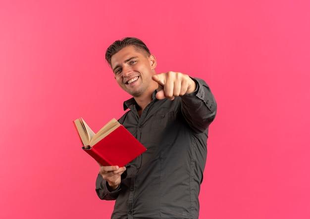 Jonge lachende blonde knappe man houdt boek en wijst naar camera geïsoleerd op roze achtergrond met kopie ruimte