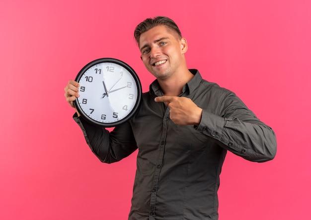 Jonge lachende blonde knappe man houdt en wijst op klok geïsoleerd op roze ruimte met kopie ruimte