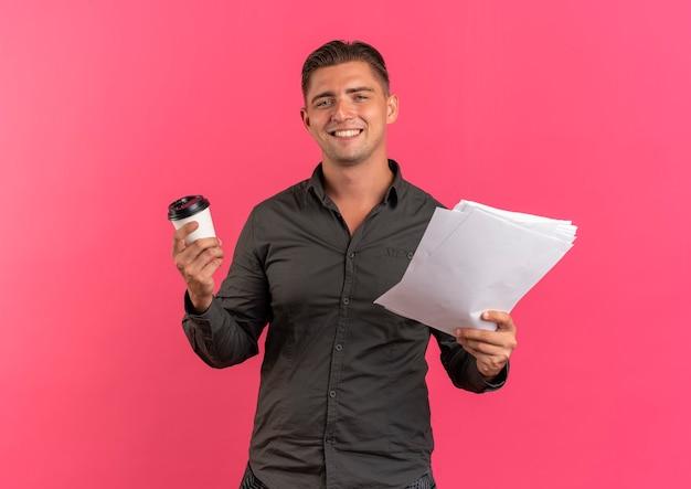 Jonge lachende blonde knappe man houdt koffiekopje en vellen papier geïsoleerd op roze achtergrond met kopie ruimte