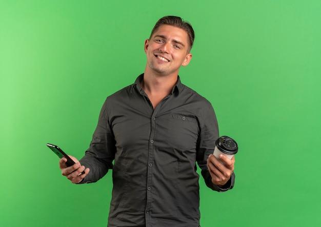 Jonge lachende blonde knappe man houdt telefoon en koffiekopje geïsoleerd op groene ruimte met kopie ruimte
