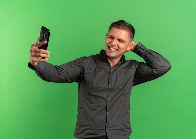 Jonge lachende blonde knappe man kijkt naar telefoon nemen selfie met hand op nek achter geïsoleerd op groene ruimte met kopie ruimte