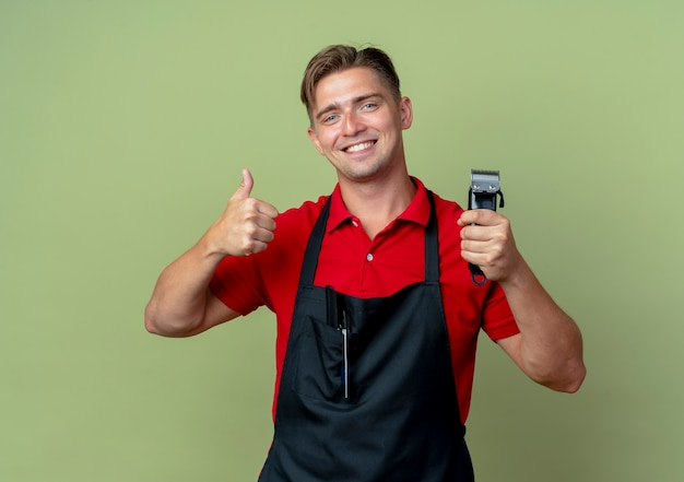 Jonge lachende blonde mannelijke kapper in uniform duimen omhoog en houdt haartrimmer geïsoleerd op olijfgroene ruimte met kopie ruimte