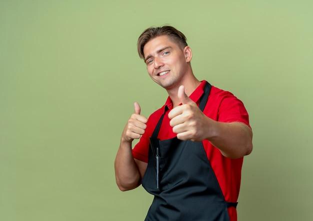 Jonge lachende blonde mannelijke kapper in uniform duimen omhoog met twee handen geïsoleerd op olijfgroene ruimte met kopie ruimte