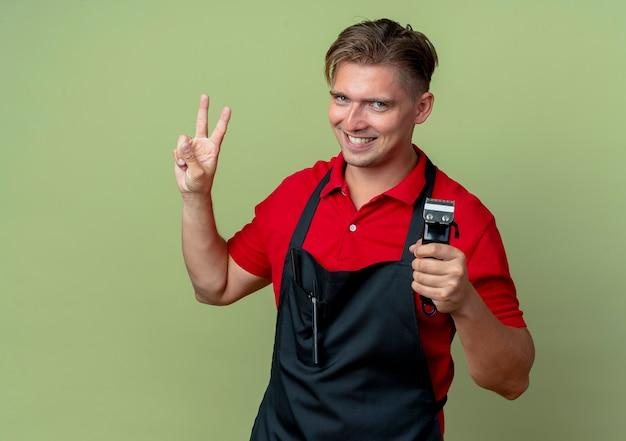 Jonge lachende blonde mannelijke kapper in uniform houdt haartrimmer en gebaren overwinning handteken geïsoleerd op olijfgroene ruimte met kopie ruimte