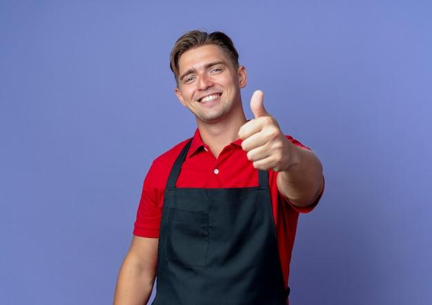 Jonge lachende blonde mannelijke kapper in uniforme duimen omhoog geïsoleerd op violette ruimte met kopie ruimte