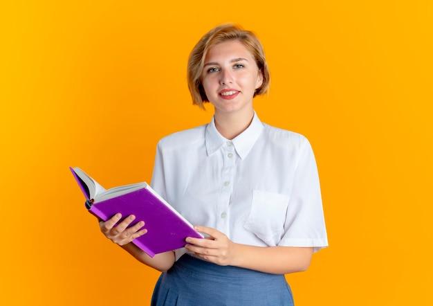 Jonge lachende blonde russische meisje houdt boek kijken camera geïsoleerd op een oranje achtergrond met kopie ruimte
