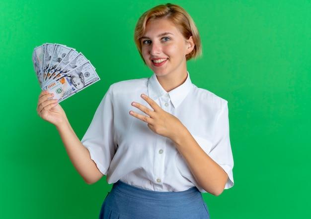 Jonge lachende blonde russische meisje houdt geld en gebaren drie met vingers