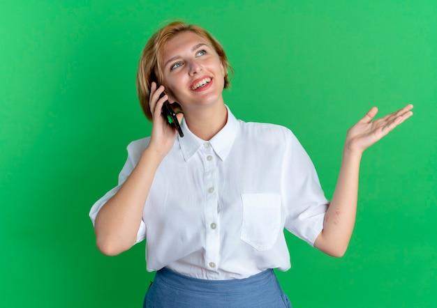 Jonge lachende blonde russische meisje praat over telefoon met opgeheven hand geïsoleerd op groene achtergrond met kopie ruimte