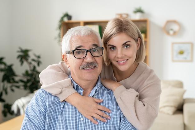 Jonge lachende blonde vrouw omarmen haar bejaarde gepensioneerde vader in brillen terwijl beide camera thuis kijken