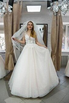 Jonge lachende bruid poseren in trouwjurk
