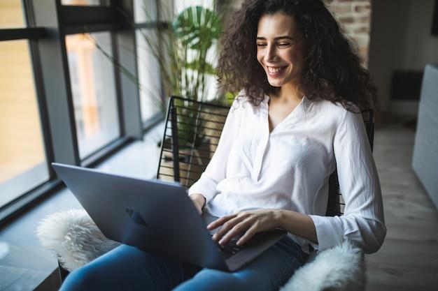 Jonge lachende brunette meisje zit op moderne stoel bij het raam in lichte, gezellige kamer thuis bezig met laptop in een ontspannen sfeer