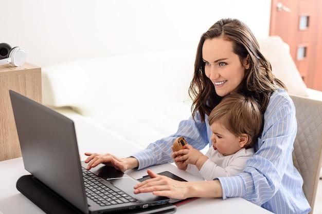 Jonge lachende brunette moeder in blauw shirt bezig met laptop met haar baby thuis, bezig met zwangerschapsverlof