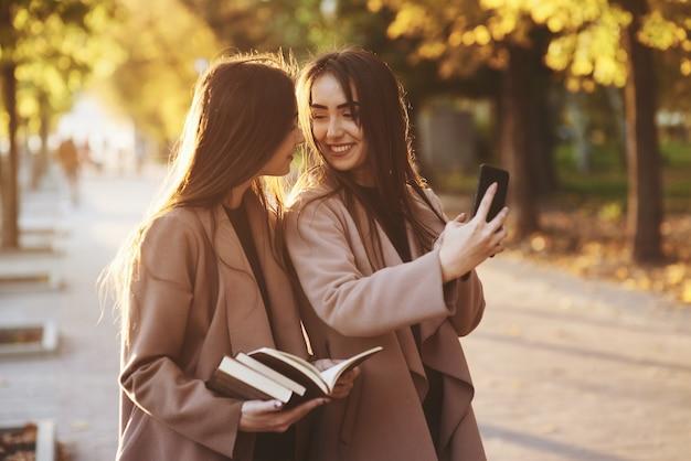 Jonge lachende brunette tweeling meisjes kijken elkaar en nemen selfie met zwarte telefoon, terwijl een van hen boeken vasthoudt, jas draagt, staande op herfst zonnige park steegje op onscherpe achtergrond.