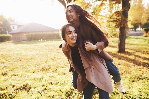 Jonge lachende brunette tweelingzusjes plezier en doen een piggy back rijden in herfst zonnig park op onscherpe achtergrond.