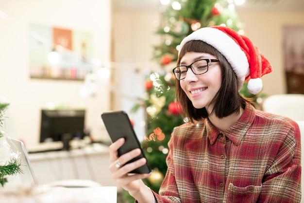 Jonge lachende brunette zakenvrouw in santa glb selfie maken door werkplek met kerstboom