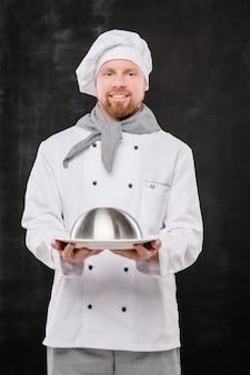 Jonge lachende chef-kok in uniform houden cloche met gekookte maaltijd voor je terwijl je geïsoleerd tegen zwarte achtergrond staat
