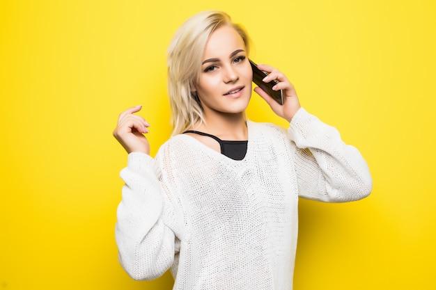 Jonge lachende dame vrouw meisje in witte trui maakt gebruik van smartphone op geel