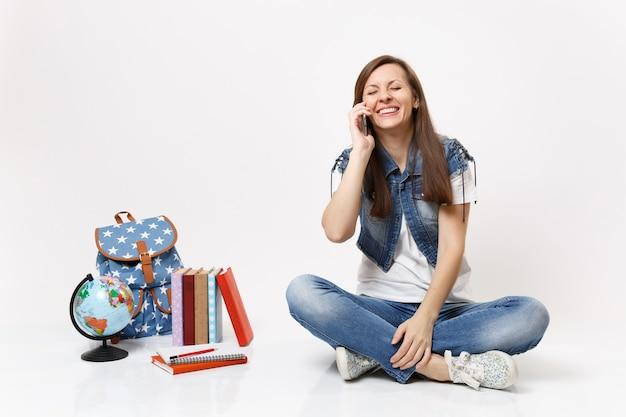 Jonge lachende dolblij studente met gesloten ogen praten op mobiele telefoon, zittend in de buurt van globe, rugzak, schoolboeken geïsoleerd