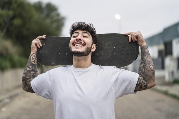 Jonge lachende europese coole man met een schaats op de wazige omgeving van een straat