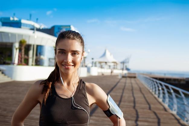 Jonge lachende fitness meisje aan zee