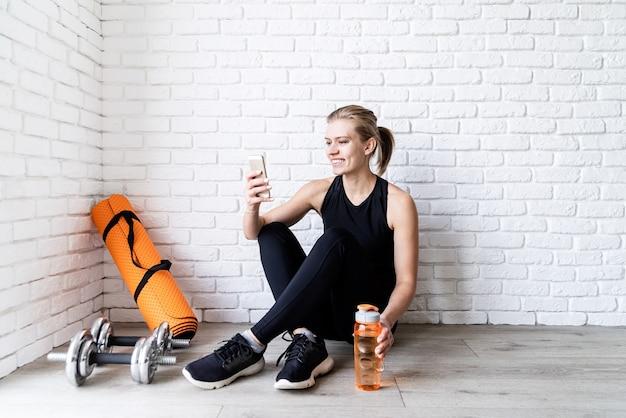 Jonge lachende fitness vrouw selfie na training zittend op het drinkwater van de vloer
